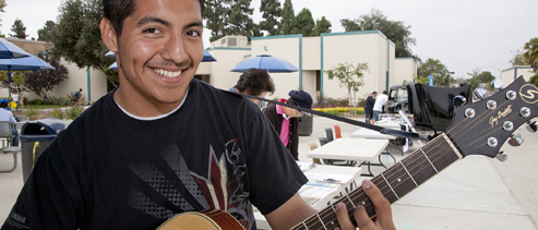 Student playing guitar outdoors
