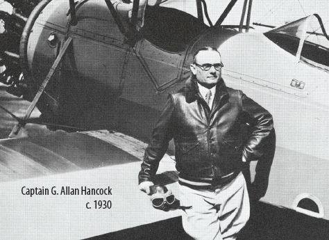 G. Allan Hancock standing next to an airplane 1930